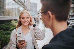 Ouple ou rire d'amis drôle et avoir l'amusement avec un téléphone intelligent dans une grande rue de ville Photo stock