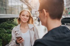 Ouple ou rire d'amis drôle et avoir l'amusement avec un téléphone intelligent dans une grande rue de ville image stock