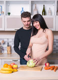 Сouple preparing food in the kitchen. Future parents Royalty Free Stock Image