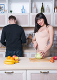 Сouple preparing food in the kitchen. Pregnant woman. Royalty Free Stock Photo