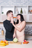 Сouple preparing food in the kitchen. Pregnant woman. Stock Photo