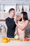 Сouple preparing food in the kitchen. Pregnant woman. Stock Image