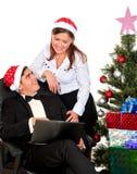 Ouple que se divierte que mira en el ordenador portátil cerca del árbol de navidad Fotos de archivo