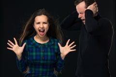 ouple som har konflikten, dåliga förhållanden Skrikig man för ilsken raserikvinna som stänger hans öron arkivbild
