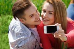 Ouples de ¡ de Ð avec le téléphone prenant l'autoportrait de selfie au parc Image stock