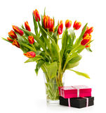 Вouquet of orange tulips on a white background. With gifts Stock Image
