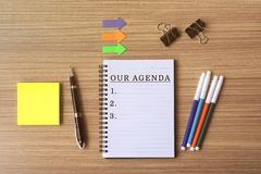 Our agenda list text on notepad. Flat lay business office desk royalty free stock photography