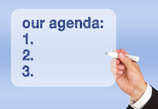 Our agenda. Text 'our agenda:' written by businessman on transparent screen, blue background stock photos