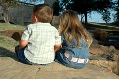 Our Backs. Brother and sister sit on a rock with their backs to the camera. Little boy and girl with their backs to the camera Stock Image