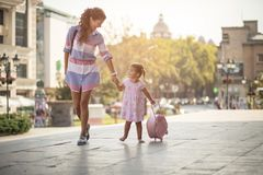 Our day begins with obligations. Mother and her little daughter walking trough city street together. Copy space stock photography