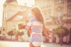 Our days are full of happiness and fun. Single mother playing with her daughter on city street. Copy space royalty free stock image