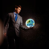 Our Earth planet. Young businessman holding Earth planet in hand. Elements of this image are furnished by NASA royalty free stock photography