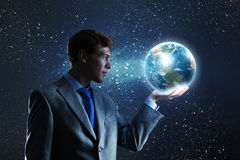 Our Earth planet. Young businessman holding Earth planet in hand. Elements of this image are furnished by NASA stock images