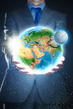Our Earth planet. Young businessman holding Earth planet in palm. Elements of this image are furnished by NASA royalty free stock photo