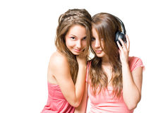Our favourite tunes. Two gorgeus brunette girls sharing music in headphones Stock Photos