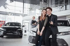 Our first car. Beautiful happy woman smiling showing the keys to a new car they just bought with her husband happy. Our first car. Beautiful happy women smiling Stock Photos