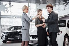 Our first car. Beautiful happy woman smiling showing the keys to a new car they just bought with her husband happy. Our first car. Beautiful happy women smiling Stock Images