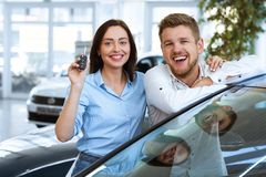 Young couple showing a key from their new car stock image
