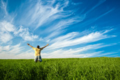 Our freedom. Man on knees in the green field  under blue skies Royalty Free Stock Photos