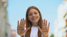 Our future in our hands written on teenage girl palms, motivational tips