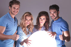 Our future will be ok!. Friends reading about their future in a crystal ball and making the ok thumbs up hand sign Stock Photo