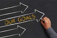 Our Goals Concept. A businessman is drawing Our Goals concept with arrows on blackboard stock photo