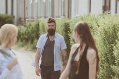 Our good friend. Bearded man meeting women on street. Boyfriend dating girlfriends. Making friends on friendship day. Our good friend. Bearded men meeting women stock photo