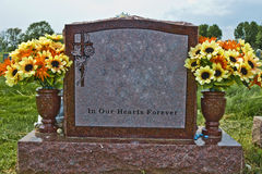 In our Hearts Forever. Memorial stone made of red granite. Inscription reads: In Our Hearts Forever. Spring / Summer flowers in the vases. Adornment in the upper stock photos