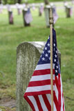 Our Heroes. The United States Flag is posted alongside a grave stone in a Veteran's Cemetery Stock Images