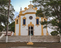 Our Lady of Remedios Church. The facade of the colonial portuguese style Our Lady of Remedios (medicine) church with its white and yellow adornments and a cross royalty free stock photo