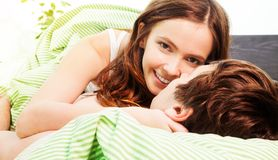 Our love games. Beautiful attractive women in the bed with her boyfriend with big smile royalty free stock image