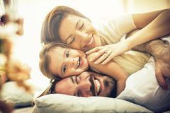 Our love is a real treasure. Happy family playing in bed. Space for copy. Close up stock photos