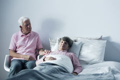 Our love is stronger than death. Senior hospice patient lying in bed and her caring husband Royalty Free Stock Photography