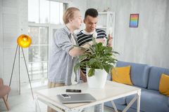 Merry gay couple taking care of plant. Our responsibility. Happy cheerful gay couple staying while caressing flower and looking down Royalty Free Stock Photography