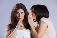 Our secret. Two female friends sharing a secret stock images