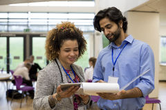 Our students are producing great work!. Two teachers are holding some paperwork in front of them and are discussing it together Stock Images