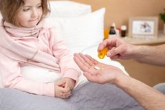 Loving father giving good pills. Our treatment. Caring worried father holding pills and giving some to his ill daughter Royalty Free Stock Image