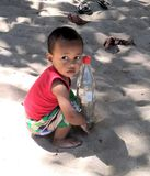 Nosy Be, Madagascar - 09/21/2018: An African child with a melancholy look holding a bottle of coke in his hands royalty free stock photography