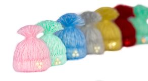 Seven beautiful multi-colored caps - handmade brooches lined up. Our view is focused on the first in a row - as if invisible athletes - children stand in a row Stock Photo