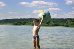 Our world in the сhildren's hands. Boy and globe on the beach Royalty Free Stock Photo
