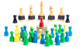 Our World - Concept. Board game pieces in front of white background - concept of our society and economic system. Workers in the front, rich business man on the Royalty Free Stock Photo