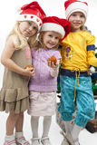 Our young Christmas team. Three young little caucasian blond girls standing together near christmas tree holding gifts and smiling sincerely.isolated over white Royalty Free Stock Photo