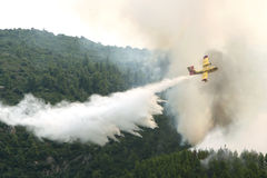 Firefighting plane. OURANOUPOLI, GREECE - AUGUST 9: A firefighting plane releases its load of water as it tries to extinguish a fire near the village of royalty free stock photo