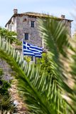 Ouranoupolis Tower on Athos peninsula in Halkidiki, flag of Greece through the palm leaves Stock Photography