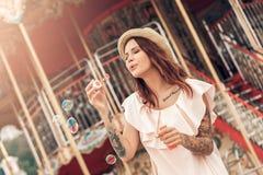 Ourdoors休闲 帽子身分的女孩在有瓶吹的泡影微笑的游乐场愉快 免版税库存照片