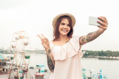 Ourdoors Leisure. Girl in hat standing near seafront taking selfie on smartphone showing peace gesture smiling happy to royalty free stock photo