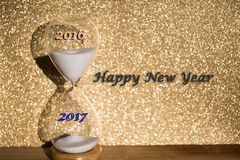 Ourglass against golden background, yearly change. New Year, Stock Image