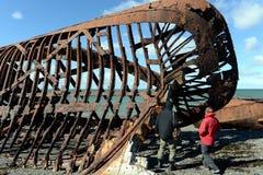 Ourists有在麦哲伦海峡的岸的一艘生锈的船在圣格雷戈里奥村庄  免版税库存照片