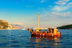 ourists, die in ein altes Schiff im adriatischen Meer nahe Dubrovnik bei Sonnenuntergang reiten Stockfoto