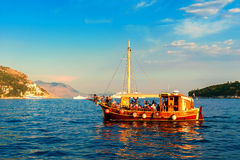 Ourists riding in an old ship in the Adriatic sea near Dubrovnik at sunset Stock Photo